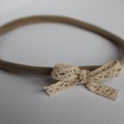 Taupe hoofdbandje met kanten strikje