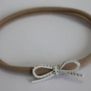 Nylon haarbandje met wit strass strikje