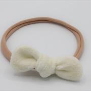 Zalmroze haarbandje met witte tricot strik